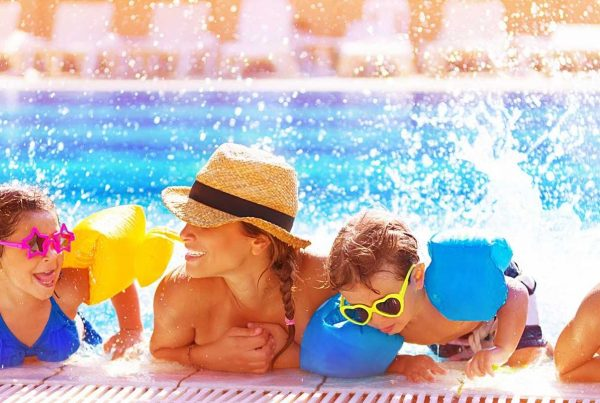 Happy family in pool after getting a pool safety certificate at All Construction Approvals