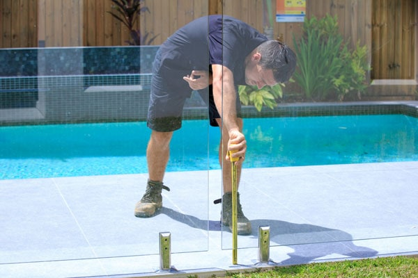 All Construction employee member performing a pool fence inspection for a pool safety certificate